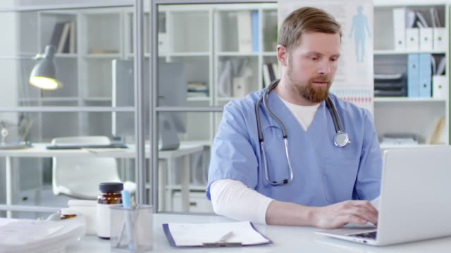 Young Male Doctor Typing on Laptop and Smiling at Camera Portrait of young male physician wearing scrubs and stethoscope over neck working on laptop at desk and then looking at camera and smiling redhead stock videos & royalty-free footage