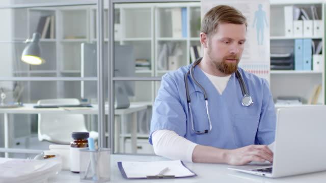 unga manliga läkare att skriva på laptop och leende på kamera - rött hår bildbanksvideor och videomaterial från bakom kulisserna