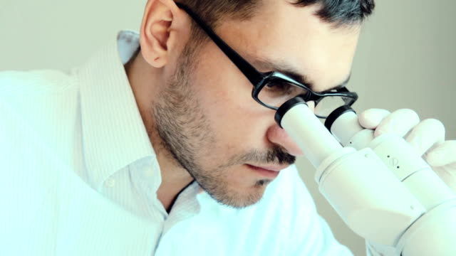 Young male doctor viewing through microscope video