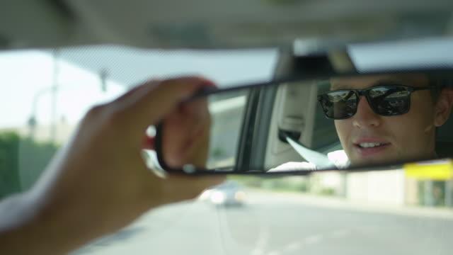 slow motion: genç erkek sürücü onun dikiz aynası ayarlamak ve kendisi de görünüyor. - ayarlamak stok videoları ve detay görüntü çekimi