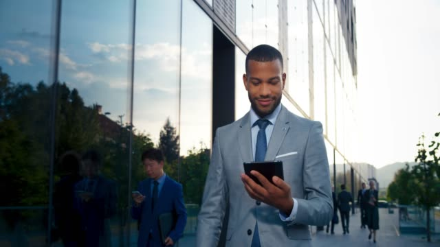 TS Young male entrepreneur working on the digital tablet while walking along the modern business building Wide low angle tracking shot of a young biracial male entrepreneur in an elegant grey suit holding a digital tablet and working on it while walking along the glass wall of a business building. Shot in Slovenia. black people stock videos & royalty-free footage