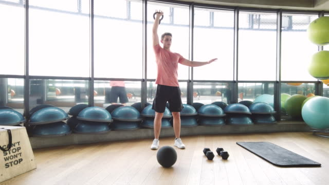 young male fitness instructor doing gym training warm up exercise with kettlebell - giria filmów i materiałów b-roll