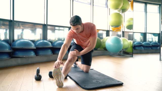 young male fitness instructor stretching legs warming up exercise - rozgrzewka filmów i materiałów b-roll