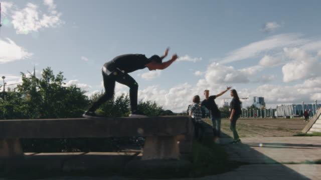 junge männliche freerunner durchführung tricks und sprünge im freien im urbanen umfeld. - stunt stock-videos und b-roll-filmmaterial
