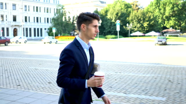 Young male going to work with his morning coffee and newspaper in hand video