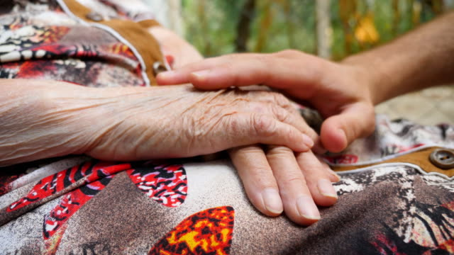 Young male hands comforting elderly arms of grandmother outdoor. Grandson and grandmother spending time together outside. Concept of caring and loving. Close up Side view Slow motion video