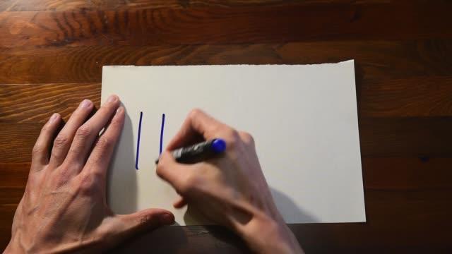 若い男性の手は、不安や抑うつの後にヘルプサインを求めるとしてホワイトペーパーにメッセージを書く上からのパニック・アタック・ビューメンタルヘルスケアのコンセプト - 支えられた点の映像素材/bロール