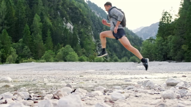 Young Male Hiker Leaping Over Water in Summertime Riverbed