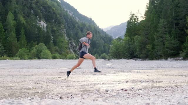 unga manliga vandrare hoppar över vatten i sommartid riverbed - endast en man i 30 årsåldern bildbanksvideor och videomaterial från bakom kulisserna