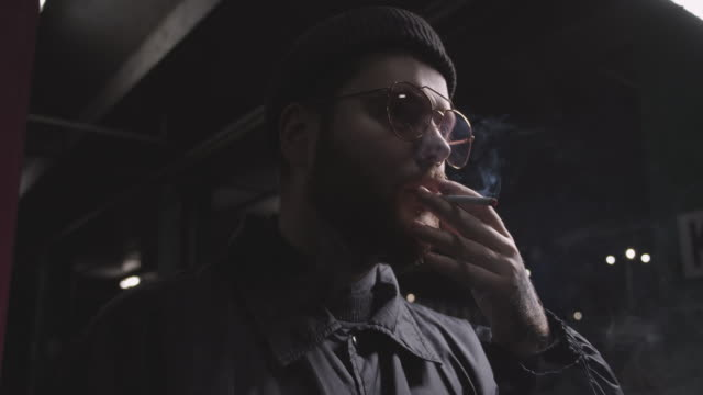 Young male hipster smoking cigarette in darkness outdoors, alone in street