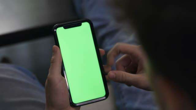 stockvideo's en b-roll-footage met jonge mannelijke holding cellphone die en groen scherm veegt en schuift - mannelijk
