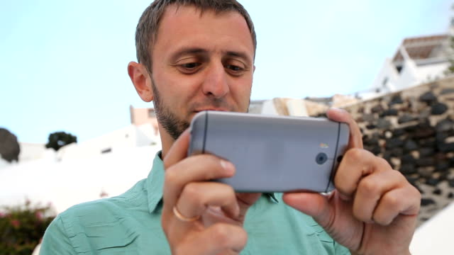 Young male holding cellphone, watching video with surprised expression, emotions video