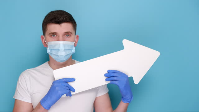 Young male in medical protective face mask and latex gloves holding paper arrow, dressed in white t-shirt, isolated on blue background with copy space for advertisement. Epidemic coronavirus concept