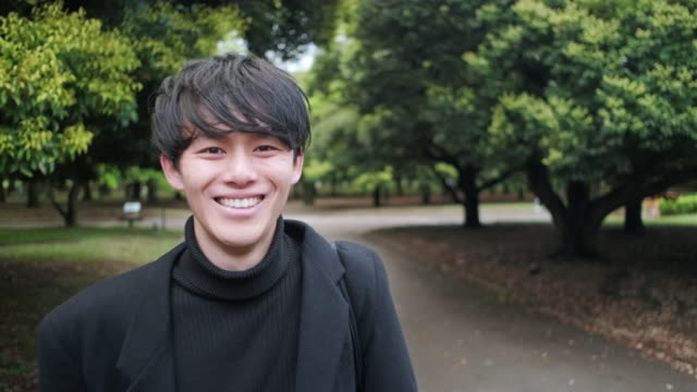 Young Male Japanese Adult at Tokyo Park Headshot video portrait of a smiling handsome young Japanese man walking through a verdant urban Tokyo public park. handsome people stock videos & royalty-free footage