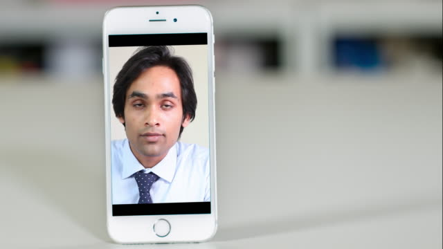 Young male lawyer listening to an off-camera client on a smart phone. video