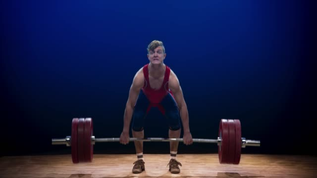 junge männliche lifter, die den sauberen und ruckreikenden lift, um die langhantel über den kopf bei einem wettbewerb zu heben - gewichtstraining stock-videos und b-roll-filmmaterial