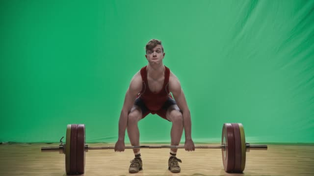 Young male lifter performing the clean and jerk lift