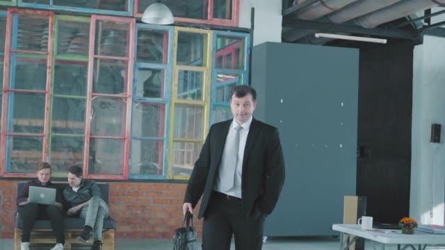 スーツを着た若い男性マネージャーがオフィスに入ってきて、フリップチャートに向かって、同僚を歓迎します。クリエイティブなオフィスインテリア。コワーキング。オフィスライフ。労� ビデオ