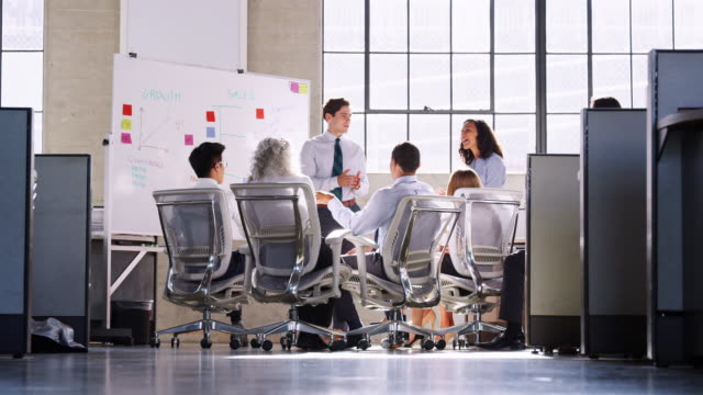 young male manager standing by a whiteboard at a meeting - lavagna bianca video stock e b–roll