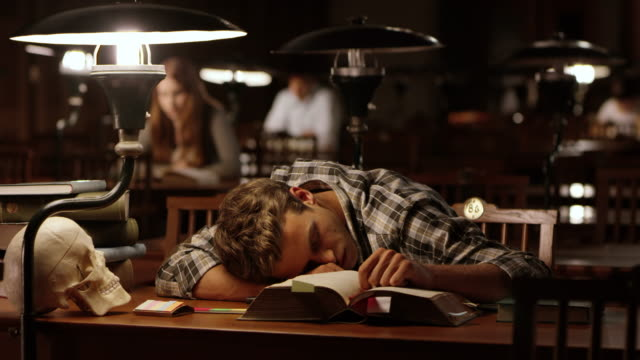 DS Young male medical student falling asleep in library video