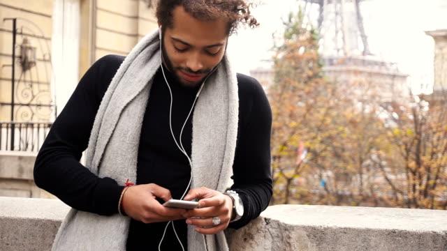 vídeos de stock, filmes e b-roll de modelo masculino jovem conversando com smartphone e ouvir música perto da torre eiffel - moda parisiense