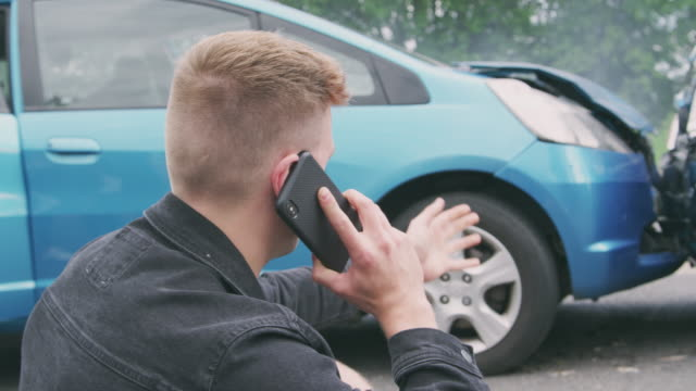 young male motorist involved in car accident calling insurance company or recovery service - incidente video stock e b–roll