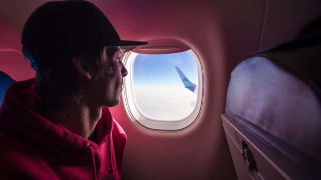 Young male passenger looking through airplane window during flight video