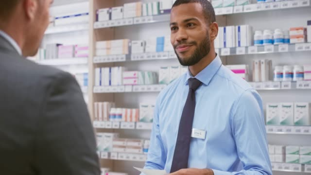 Young male pharmacist being handed a prescription by a male business man