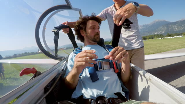 LD Young male pilot buckling his harness before the take off in his glider with a passenger behind him