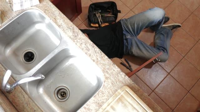 vidéos et rushes de jeune plombier mâle s'asseyant sur le plancher et remplaçant le tuyau de piège sous un évier de salle de bains - cuisine non professionnelle