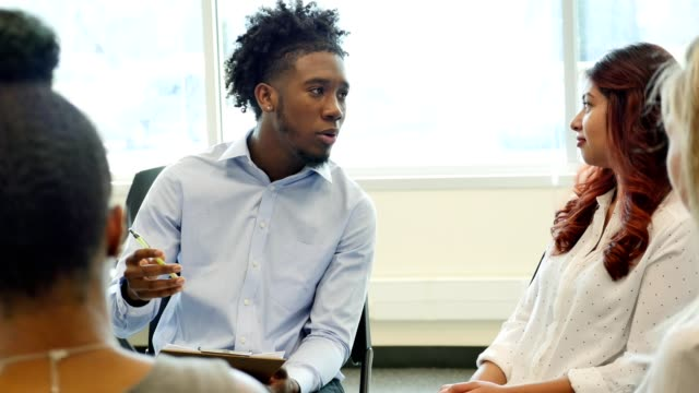 Young male psychologist facilitates a group therapy session Handsome young African American male psychologist talks with a young woman during support group or group therapy session. He is holding a clipboard as he gestures while asking the woman a question. She nods her head while talking with the psychologist. guidance stock videos & royalty-free footage