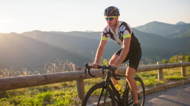 young male road cyclist cycling uphill - triatleta video stock e b–roll