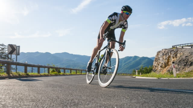 young male road cyclist pushing himself to reach the top of the mountain pass - evento ciclistico video stock e b–roll