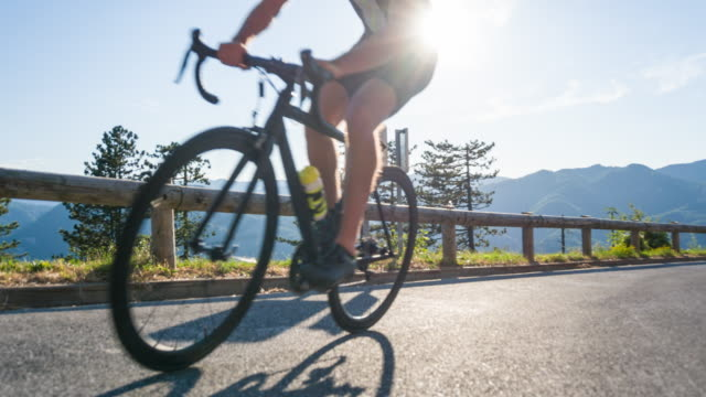 young male road cyclist pushing himself to reach the top of the mountain pass - triatleta video stock e b–roll