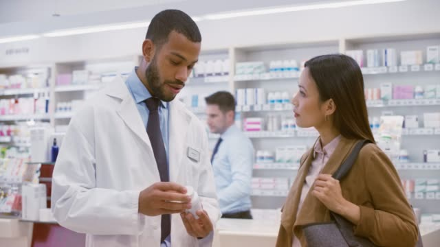 Young male salesperson advising an Asian woman about a supplement he is holding in his hand
