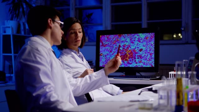 Young male scientist making notes and giving test tube with red liquid to female colleague showing him magnified microorganisms on computer screen in biochemistry laboratory