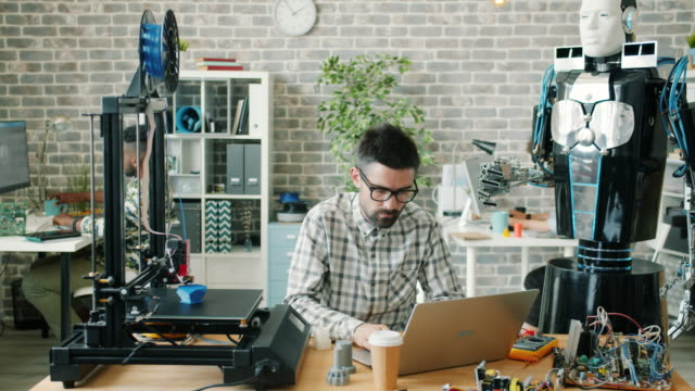 Young male scientist working with robot, laptop and 3d printer in workplace
