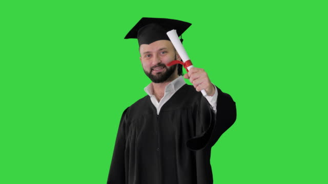 Young male smiling graduate showing thumb up on a Green Screen, Chroma Key Medium shot. Young male smiling graduate showing thumb up on a Green Screen, Chroma Key. Professional shot in 4K resolution. 4151. You can use it e.g. in your commercial video, business, presentation, broadcast diploma stock videos & royalty-free footage