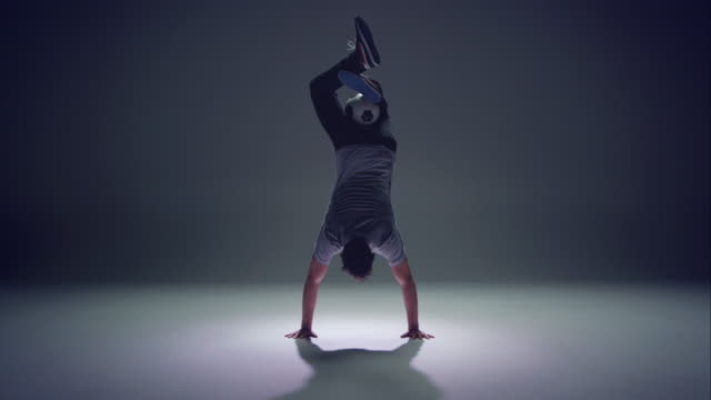 young male soccer freestyler is doing a handstand. video