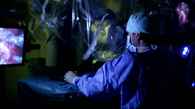 Young male surgeon operating Young male surgeon operating with a modern robotic surgery machine operating stock videos & royalty-free footage