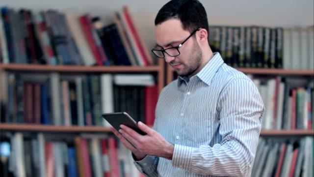 Jonge mannelijke leraar hand houden en met behulp van de tablet in de klas video