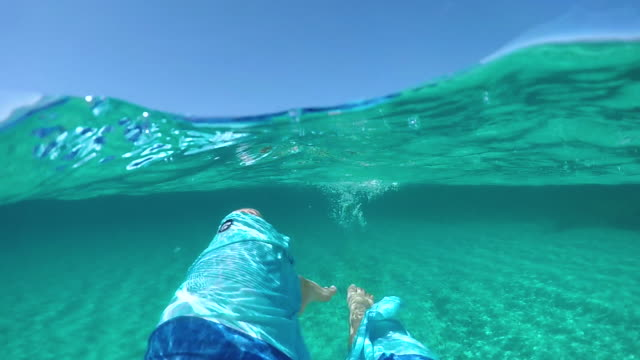slow motion: young male tourist in blue shorts kicking and swimming in the sea. - sardegna video stock e b–roll
