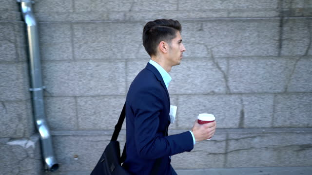 Young male walking on the street and holding his coffee and newspaper video