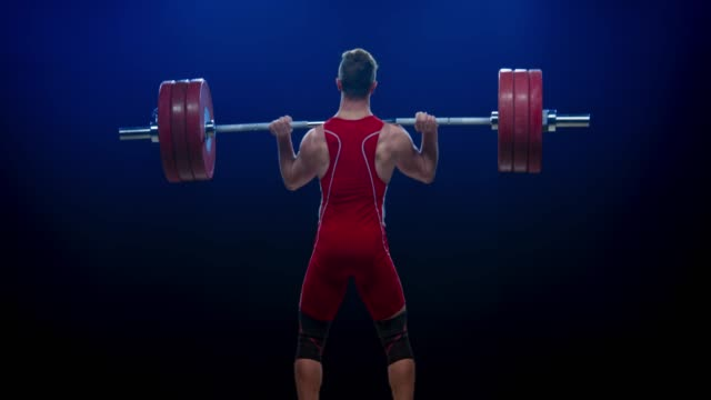 young male weightlifter performing the clean and jerk lift to lift the barbell at a competition - body abbigliamento sportivo video stock e b–roll