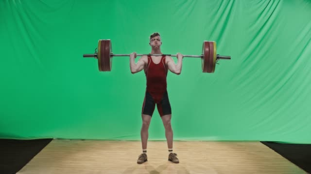 ld young male weightlifter performing the clean and jerk lift - posizione fisica video stock e b–roll