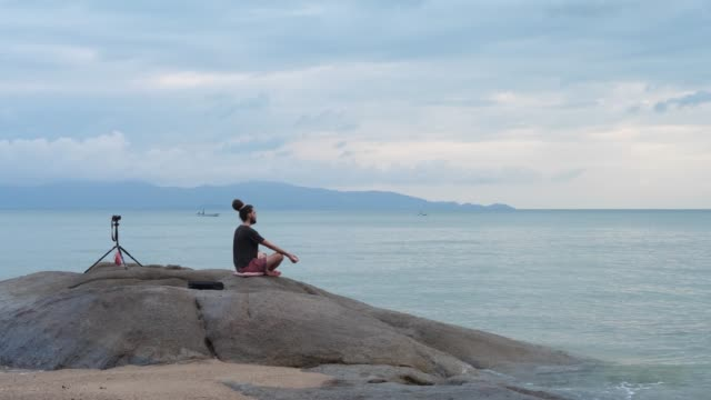 Young Male With Dreadlocks Meditates In Lotus Pose On Rock By Sea And Records Himself With Camera Man in black t-shirt with dreadlocks sits in lotus position on rock and films himself with camera on tripod in front of blue sea. Hands on knees. Blue sky and mountains layout background cross legged stock videos & royalty-free footage