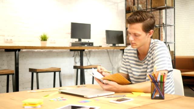 junger mann schreiben in notizbuch mit stift, moderne loft-büro - feedback stock-videos und b-roll-filmmaterial