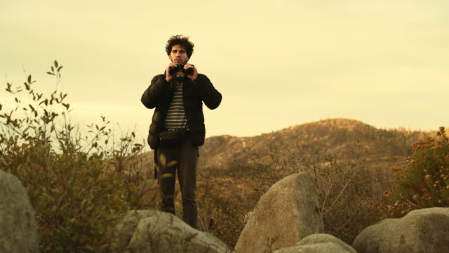 Young man, 25-years-old traveling hipster, observing the nature with the binocular from the elevated rocky point near by Devil Dance Floor in the Yosemite National Park video