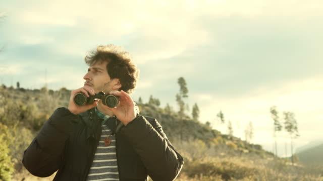 若い男が、25 歳のヒップスター、悪魔のダンス ・ フロアでヨセミテ国立公園に近く高架のロッキー ポイントから両眼と自然観察の旅 - 自然旅行点の映像素材/bロール