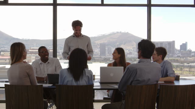 Young man addressing happy colleagues in boardroom, close up video